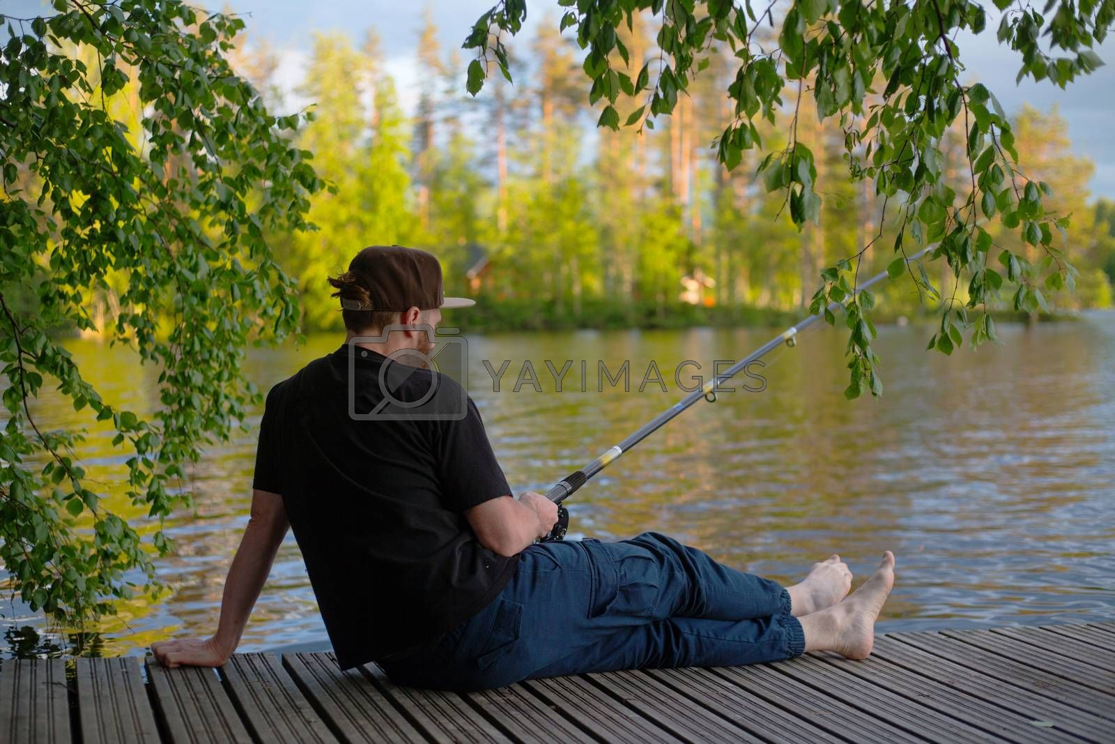 Mature man fishing from wooden pier near cottage on lake in Finland at summer