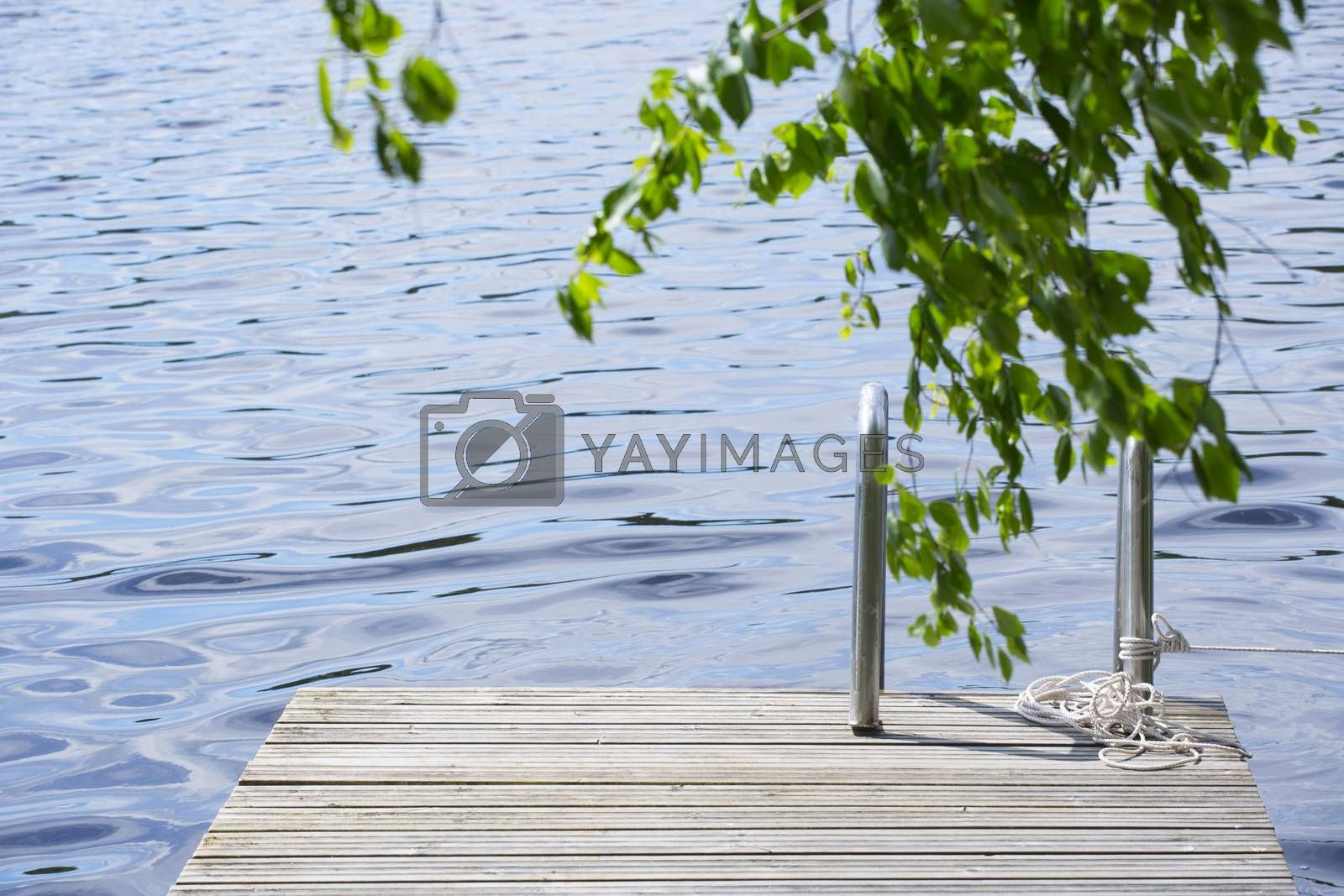 Wooden walkway jetty pier with railing for swimming in lake in Finland
