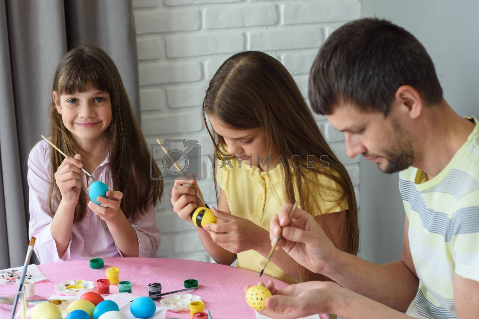 Family paints easter eggs on easter holiday