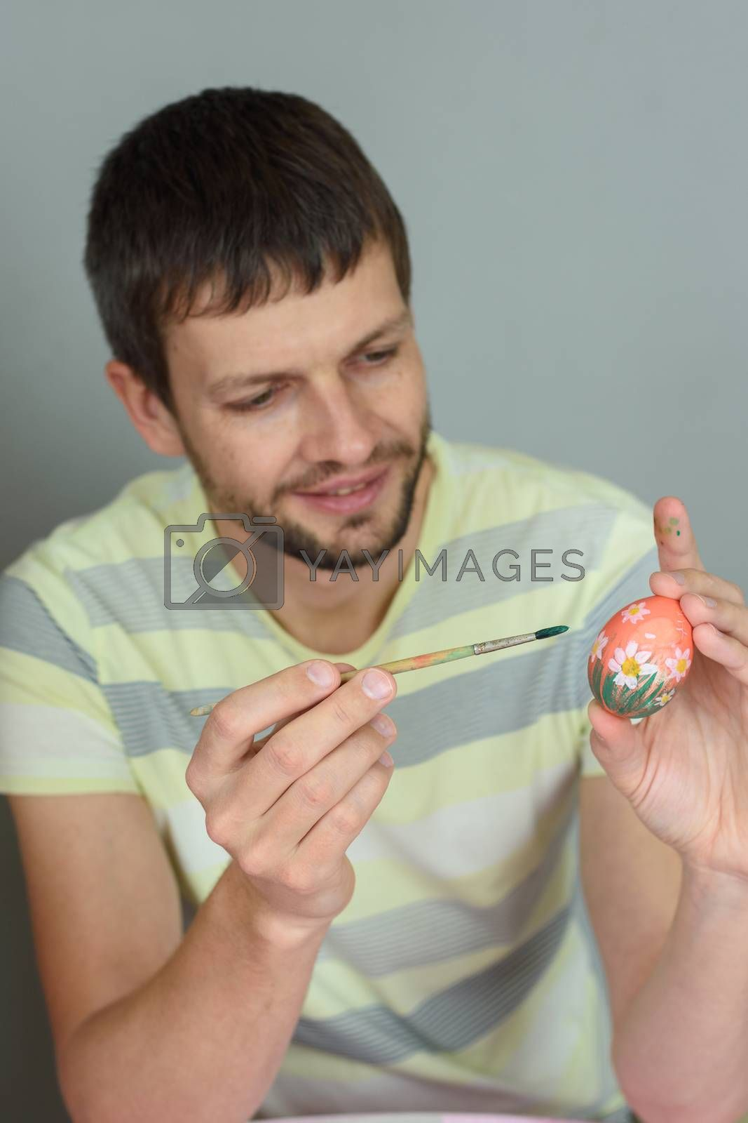 Man paints an Easter egg with a brush