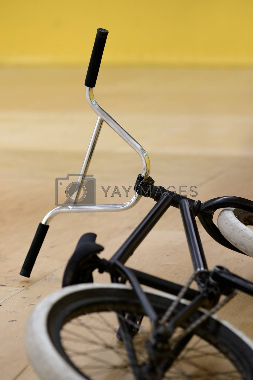Black BMX Bicycle Lying on the Wooden Floor in the Bike and Skatepark Indoor. Healthy and Active Lifestyle Concept.