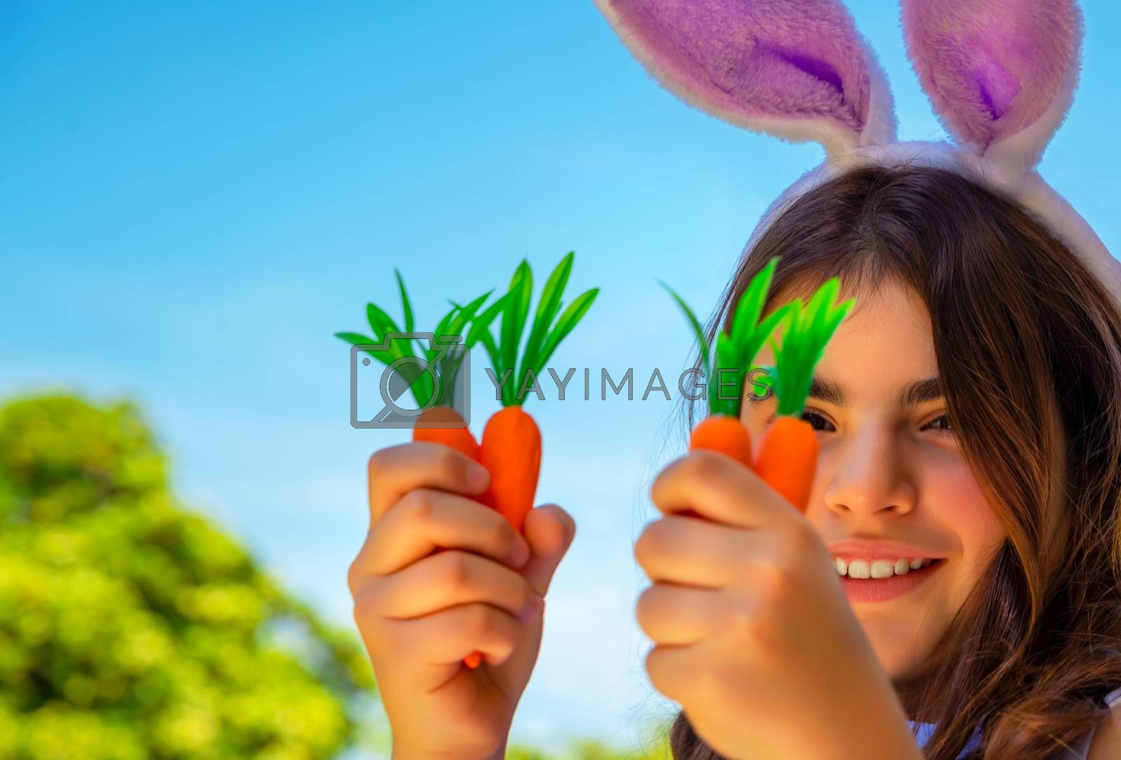 Portrait of a cute little bunny girl with carrots enjoying Easter, having fun gardening in the yard on a sunny day, traditional food for Easter celebration, happy spring holiday