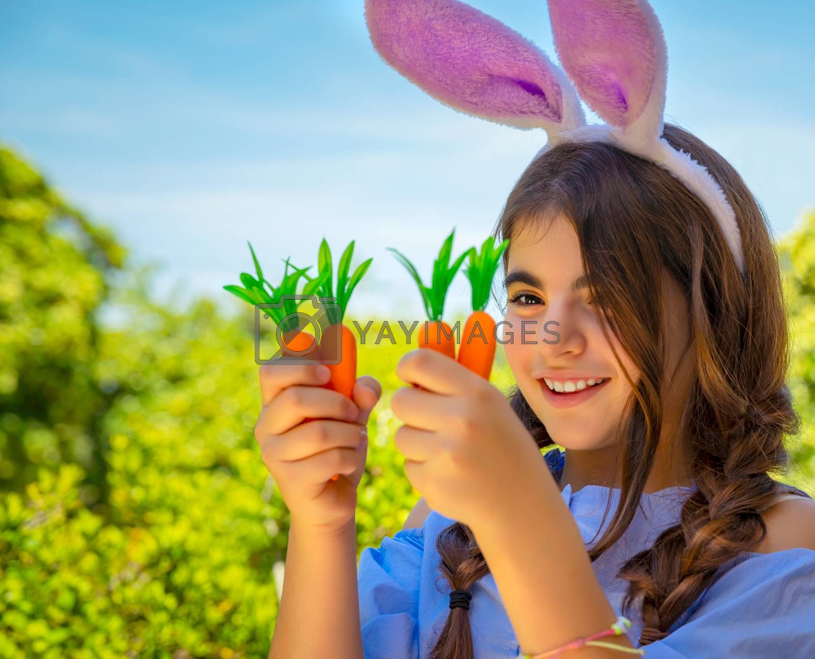 Portrait of a cute little bunny girl with carrots in hands enjoying Easter, having fun gardening in the yard on a spring sunny day, traditional outfit for Easter celebration, happy holiday