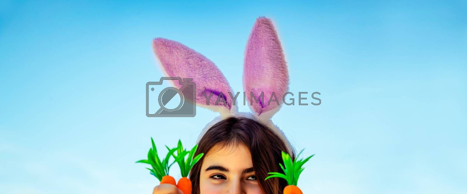 Closeup portrait of a pretty girl wearing cute pink bunny ears, blue sky background, happy spring holiday, traditional food for Easter, kids gardening concept