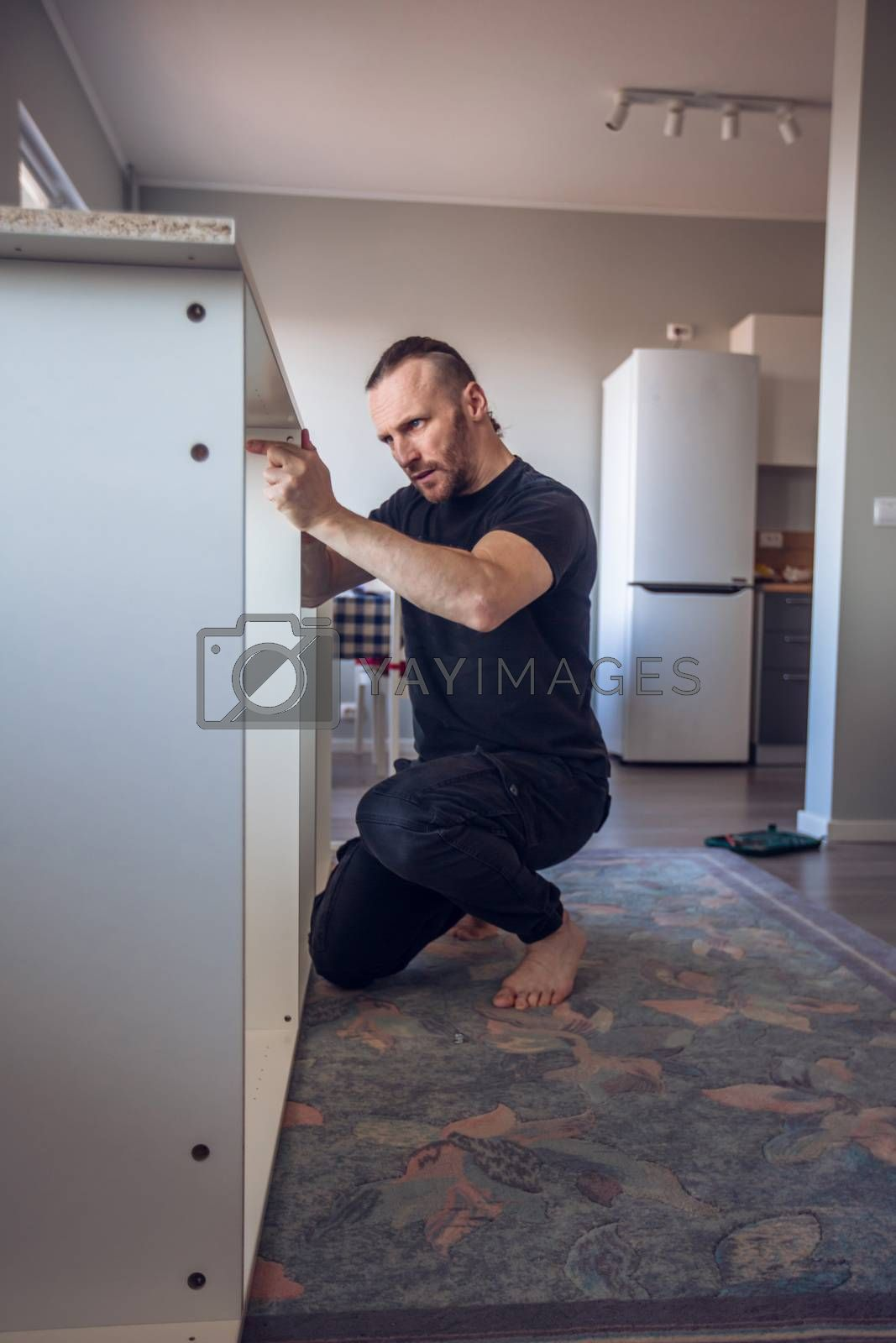 Man assembling flat pack furniture at home quarantine stay home renovation skill concept