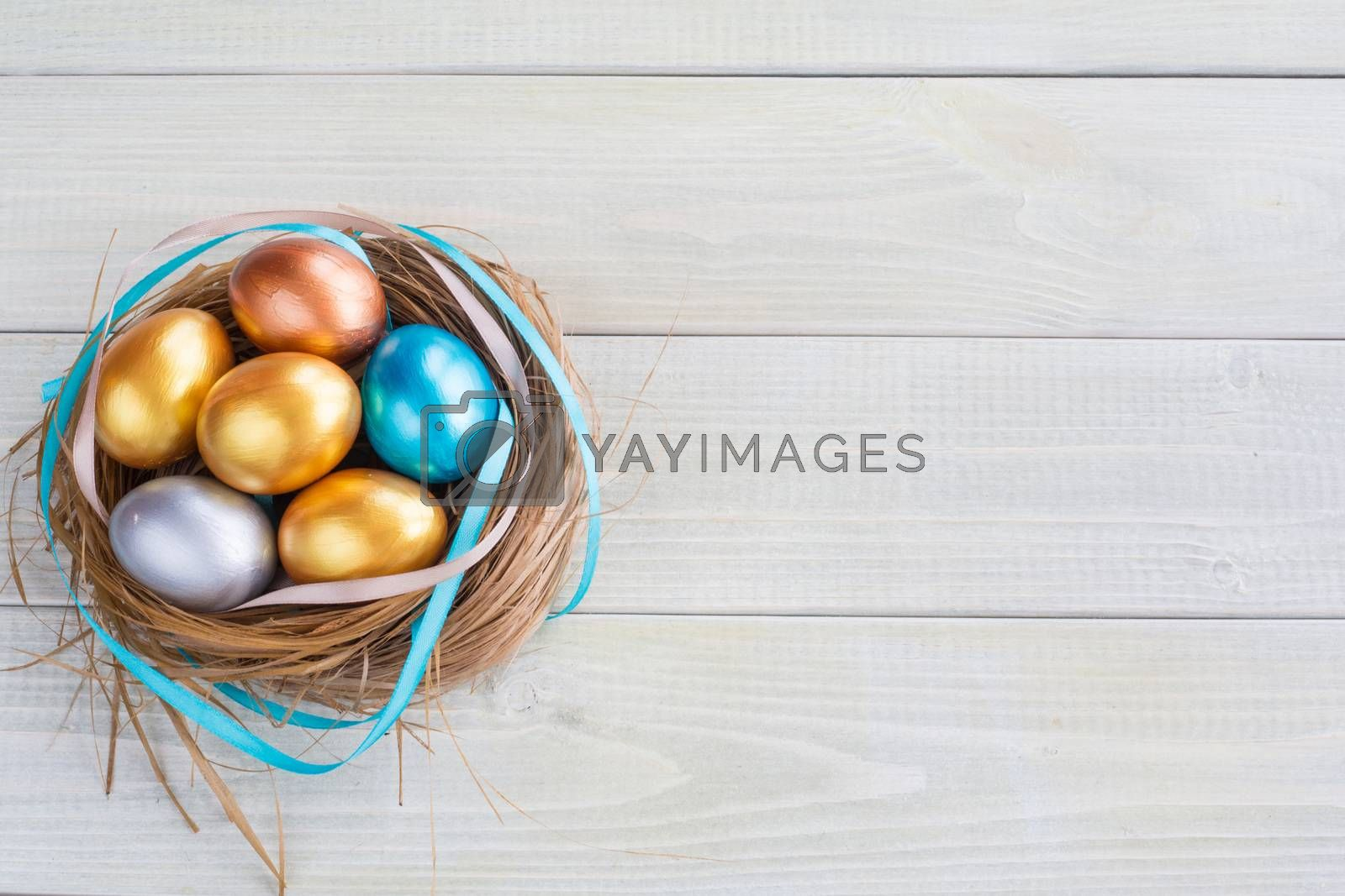 Beautiful Happy Easter holiday greeting banner with easter nest with colored eggs and decorated with ribbons over light wooden background with copy space for text