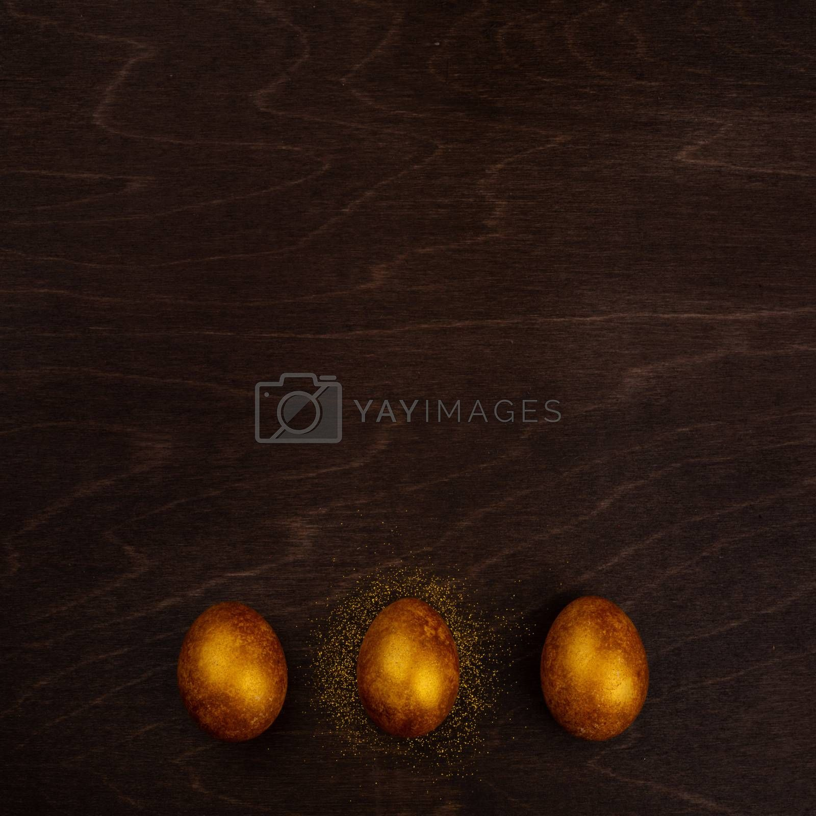 Three big golden easter eggs on dark wooden background copy space for text