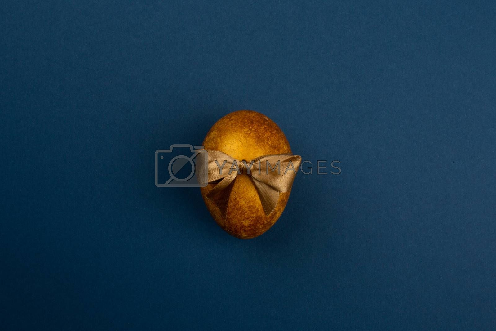 One big golden easter egg with ribbon bow on blue background copy space for text