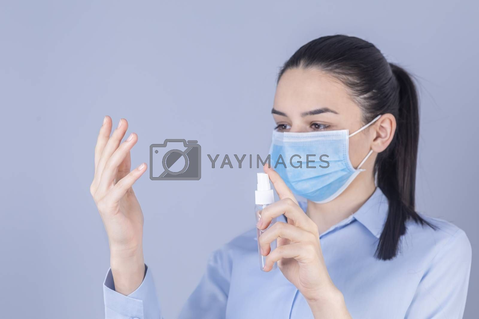 COVID-19 Pandemic Coronavirus. Girl with protective mask holdding alcohol spray cleaning protect disease covid 19. Antiseptic, Hygiene and Healthcare concept. Focus on hand.