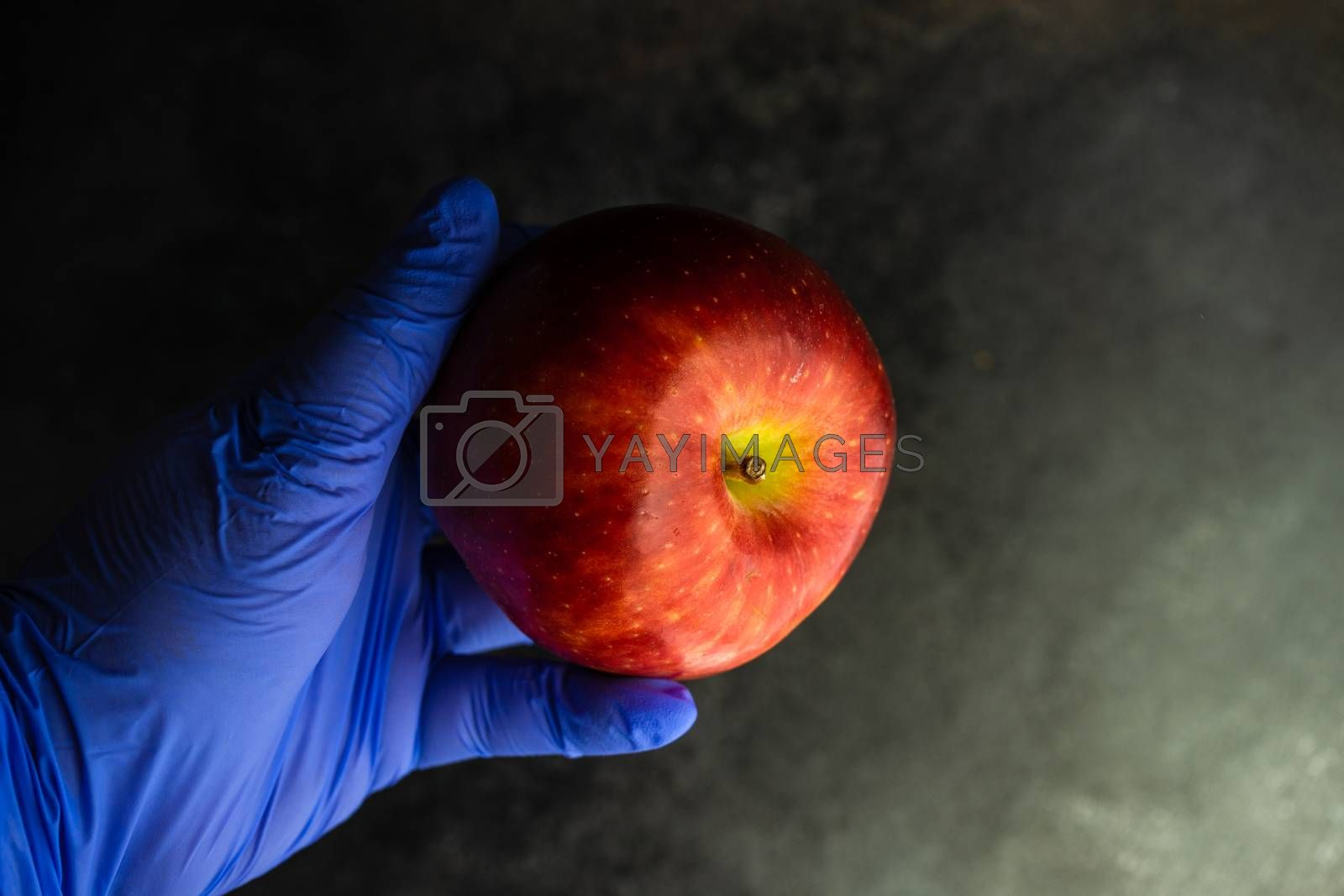 Coronavirus or Covid-19 epidemic healthcare concept with red apple in the doctor hands  on stone background with copy space
