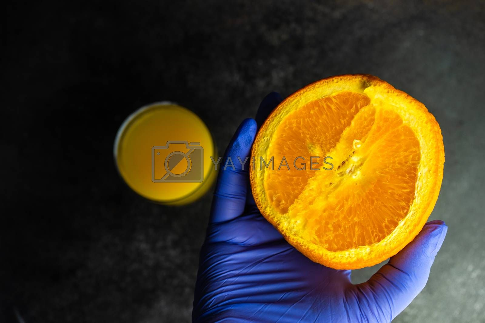 Coronavirus or Covid-19 epidemic healthcare concept with glass of citrus juice in the doctor's hands on stone background with copy space