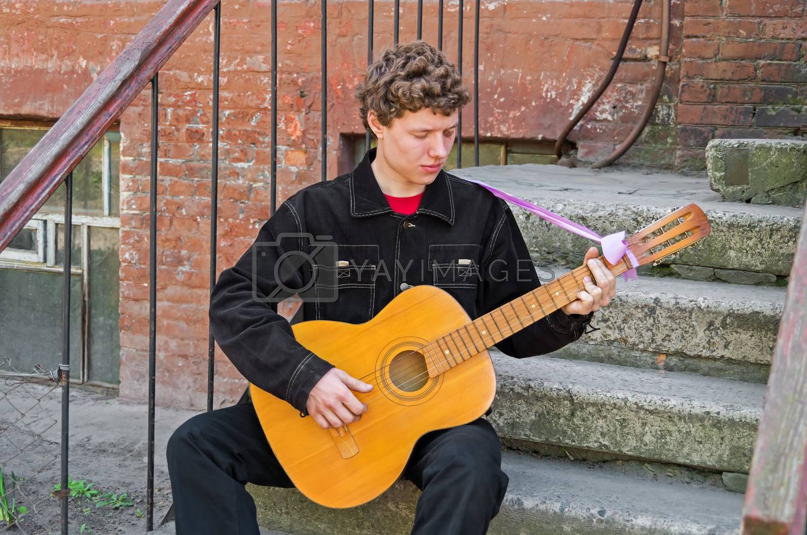 Guitarist playing his guitar of classical musical instrument on the street.
