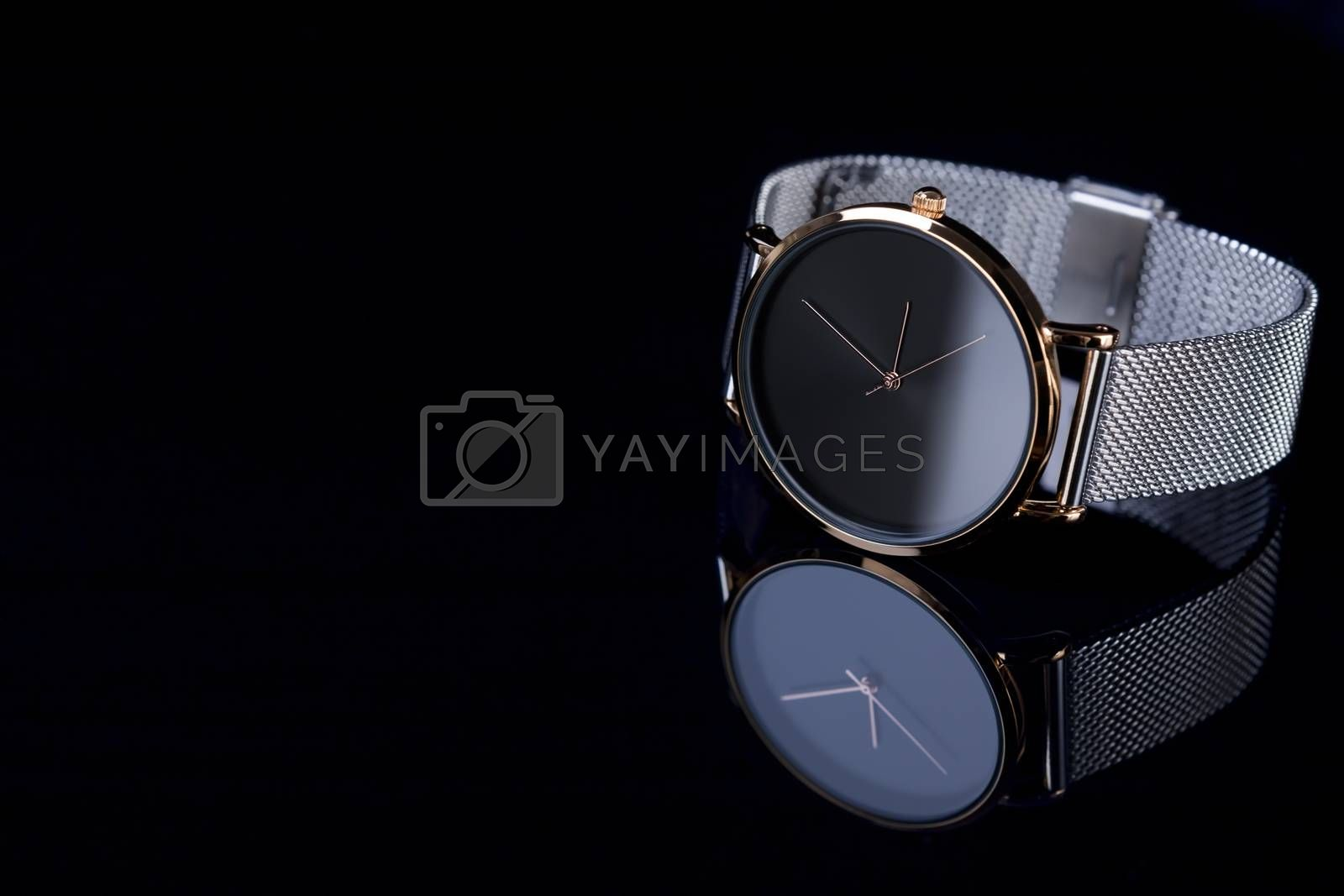 Black wrist watch for women with metal bracelet on glossy black background.