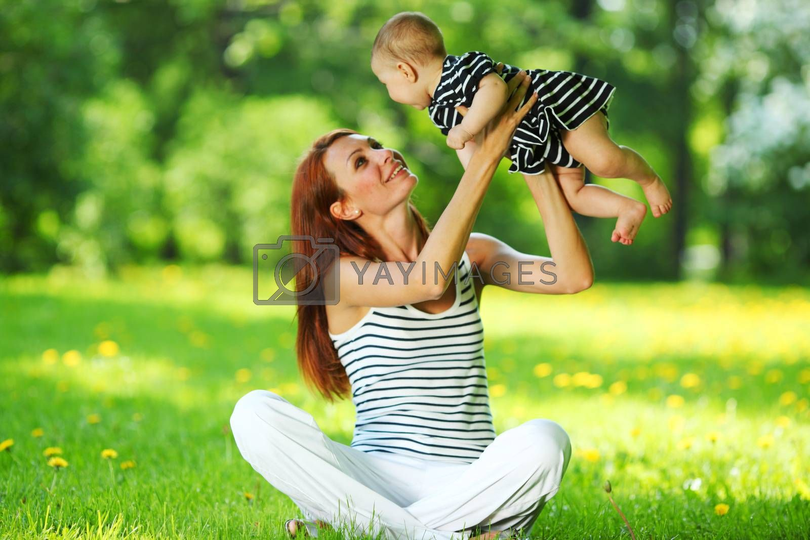 Happy mother and daughter on the green grass in summer park