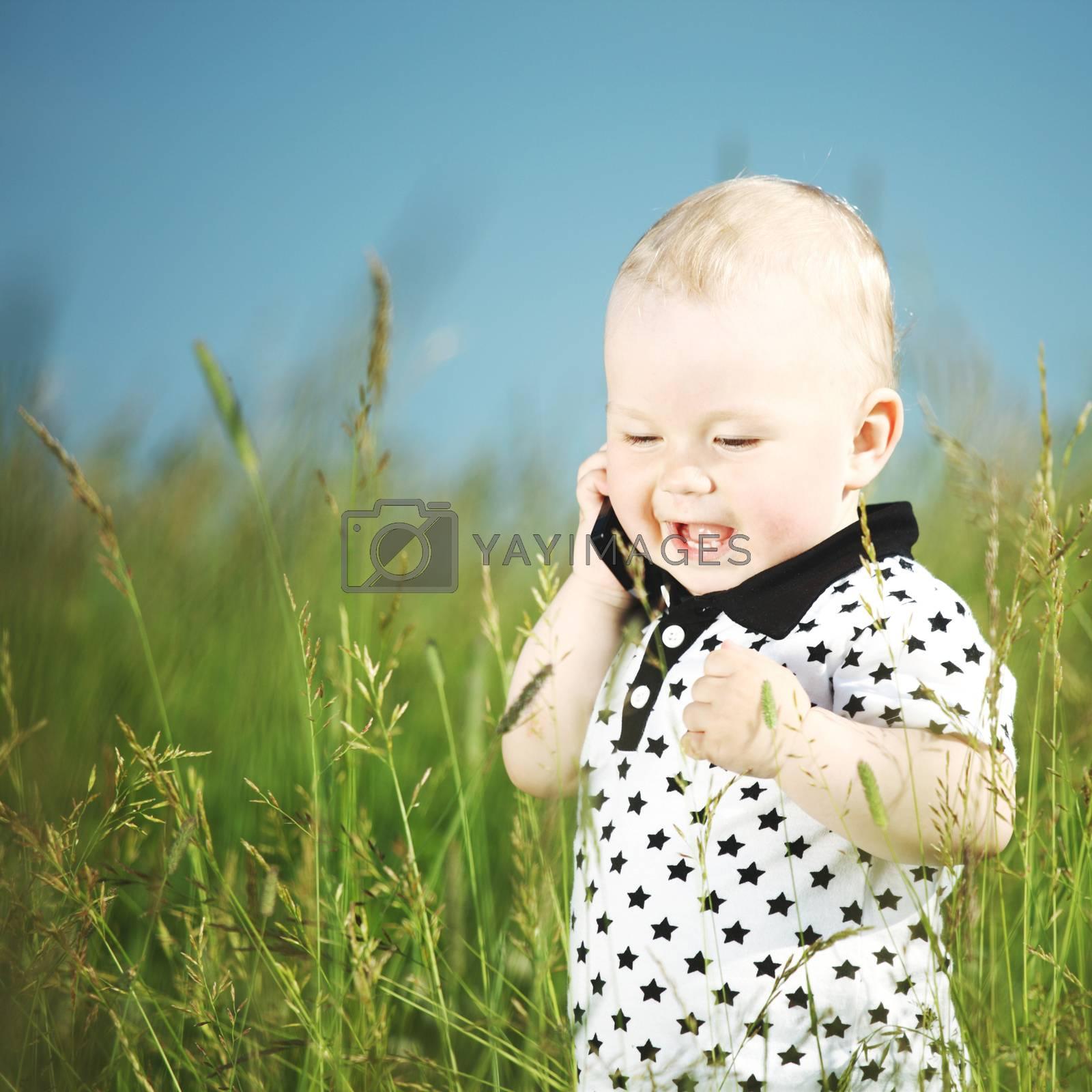 Little cute boy in green grass meadow call by phone