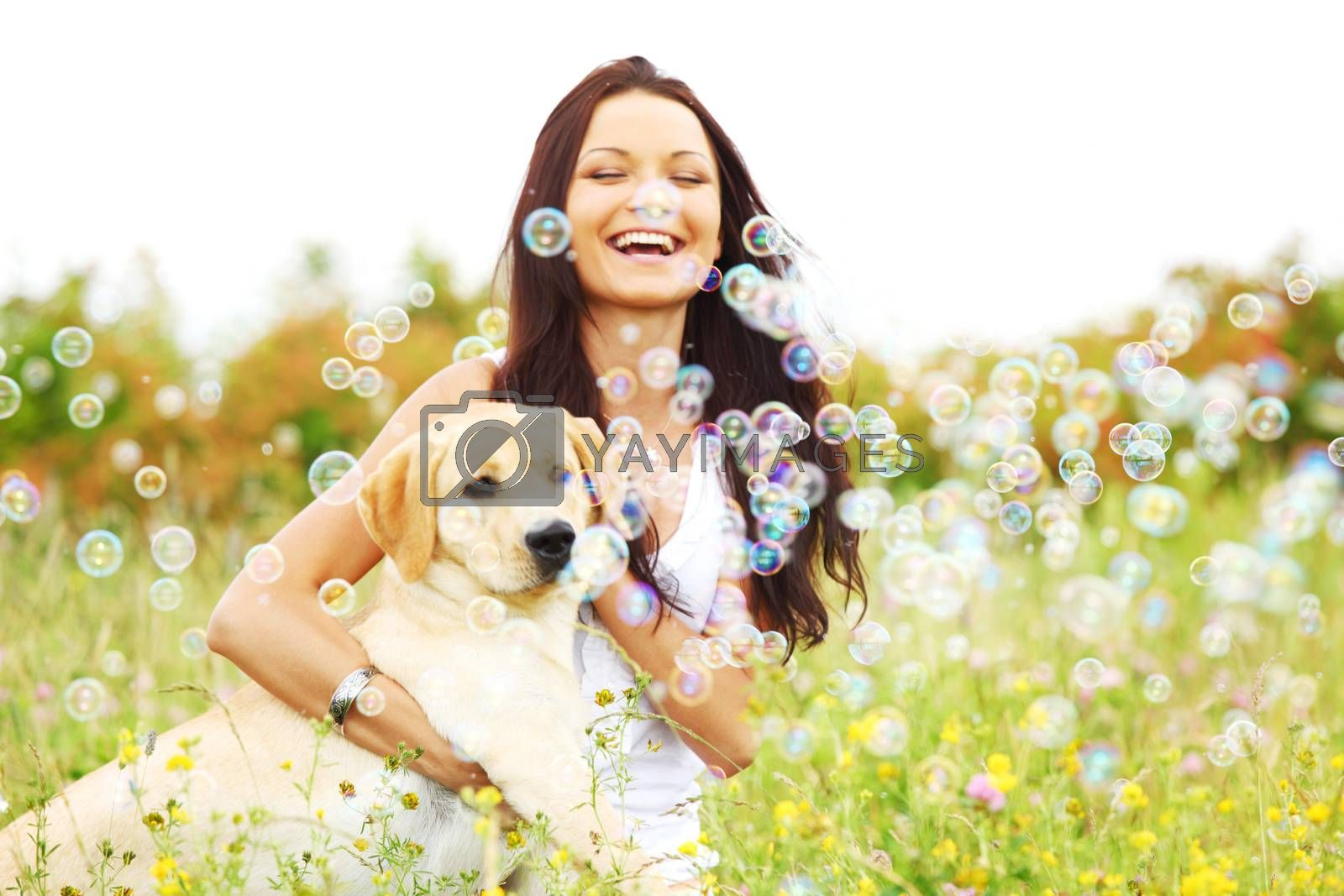 Happy woman and her lablador dog in green grass meadow