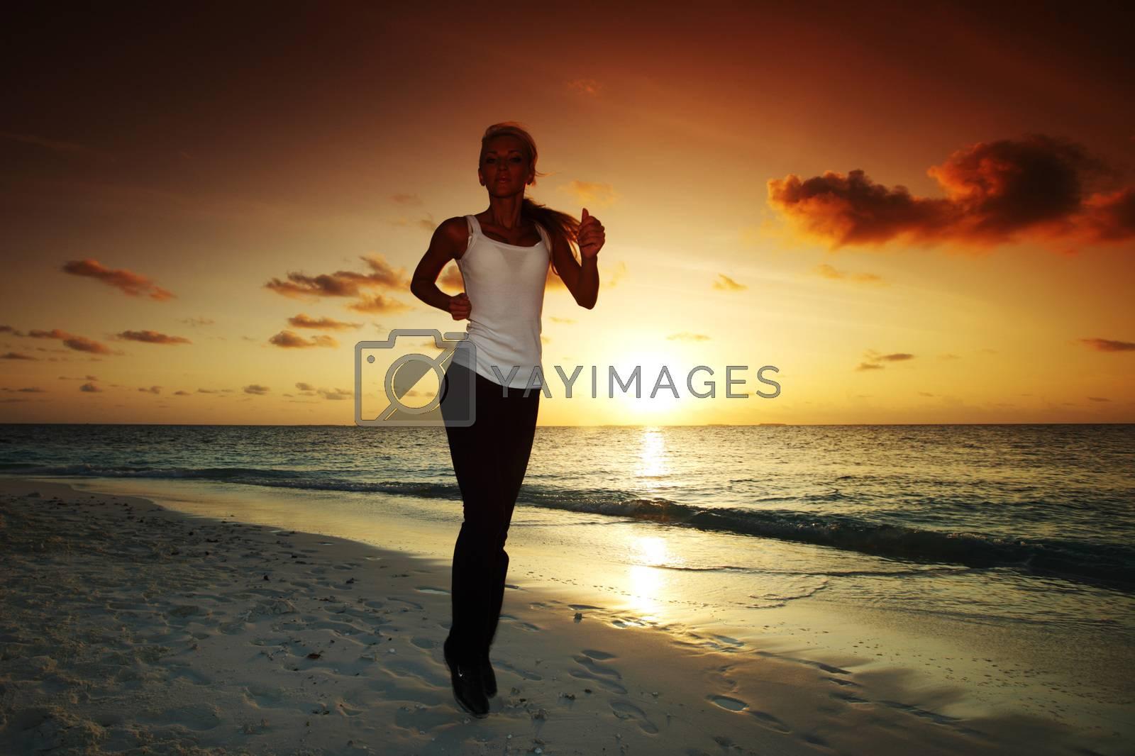 Woman run along the sea coast of sunrise or sunset behind