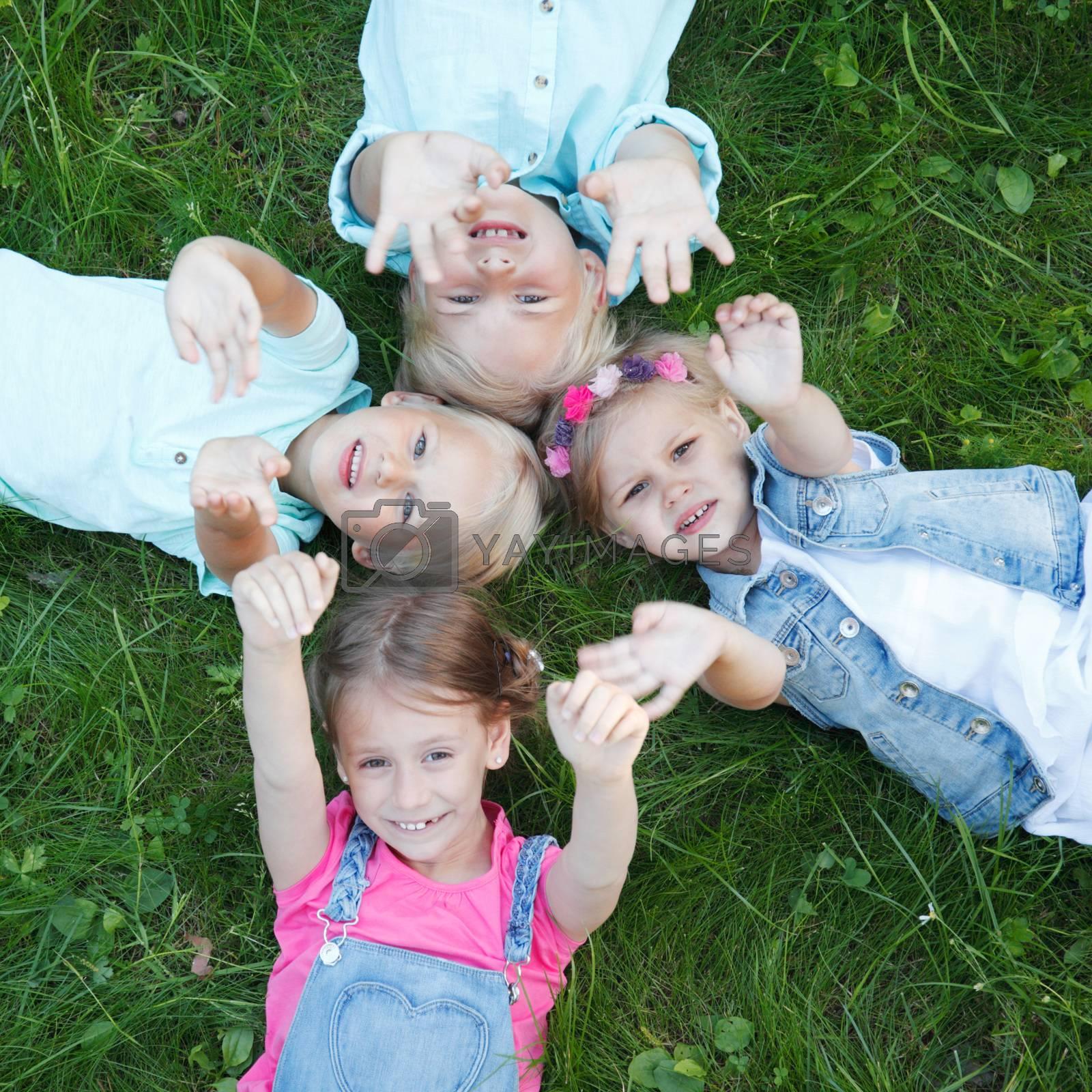 Little children friends laying on grass in summer park top view