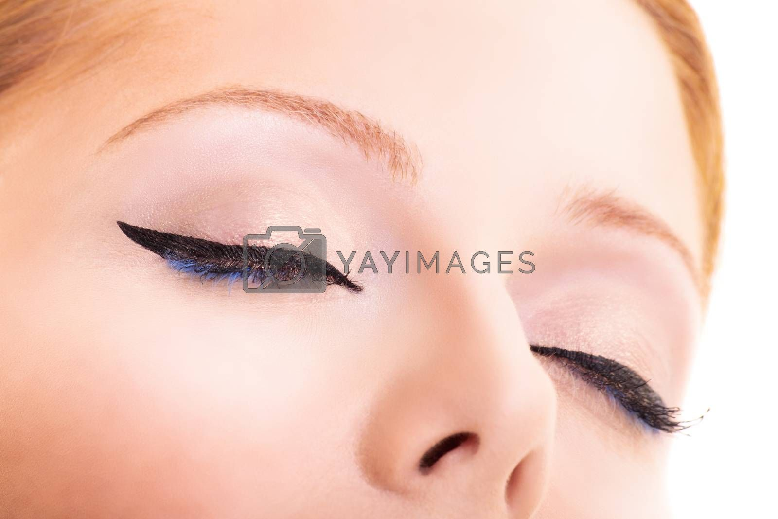 Close-up beauty shot of pretty young model with classic eyeliner, black and blue mascara, glowing clean skin and blond hair. Beauty and make up concept. Closeup macro shot of fashionable eyeliner on closed eyes.