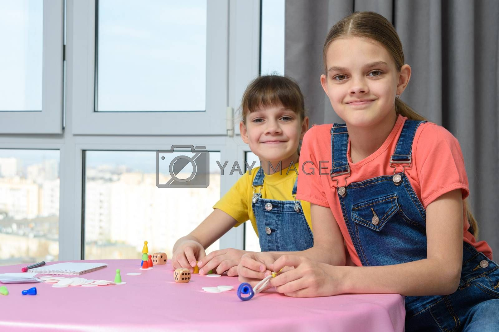 Two girlfriends play board games for children and looked at the frame