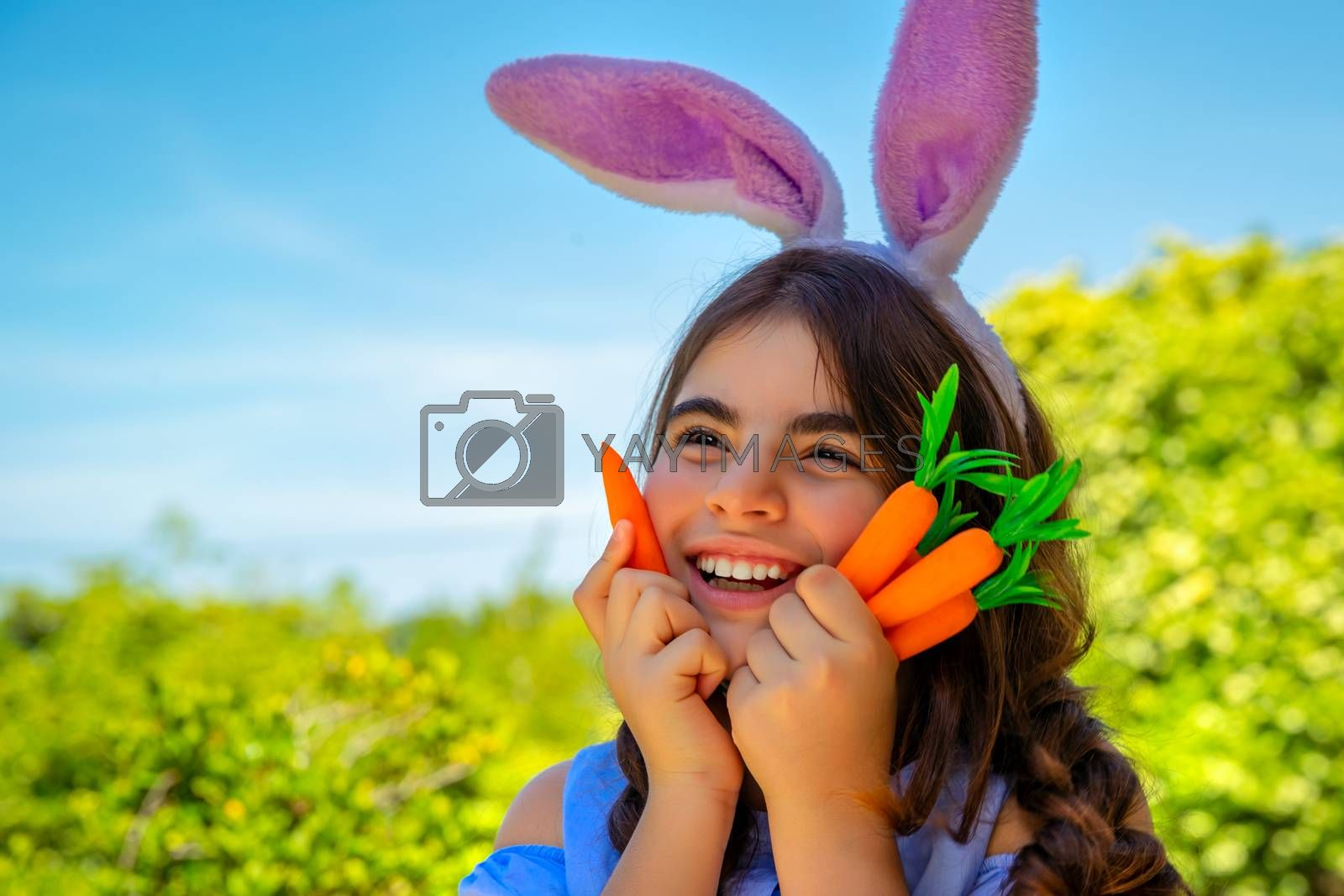 Portrait of a cute little bunny girl with carrots in hands enjoying Easter, having fun gardening in the yard on a spring sunny day, traditional outfit for Easter celebration, happy Christian holiday