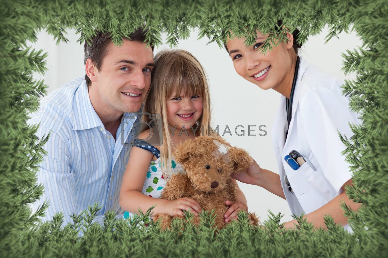 Portrait of a doctor and happy little girl examing a teddy bear against green fir branches