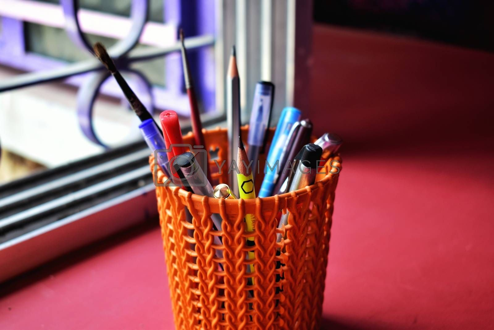 An orange colored pen case with many types of pens and pencils and some paint brush
