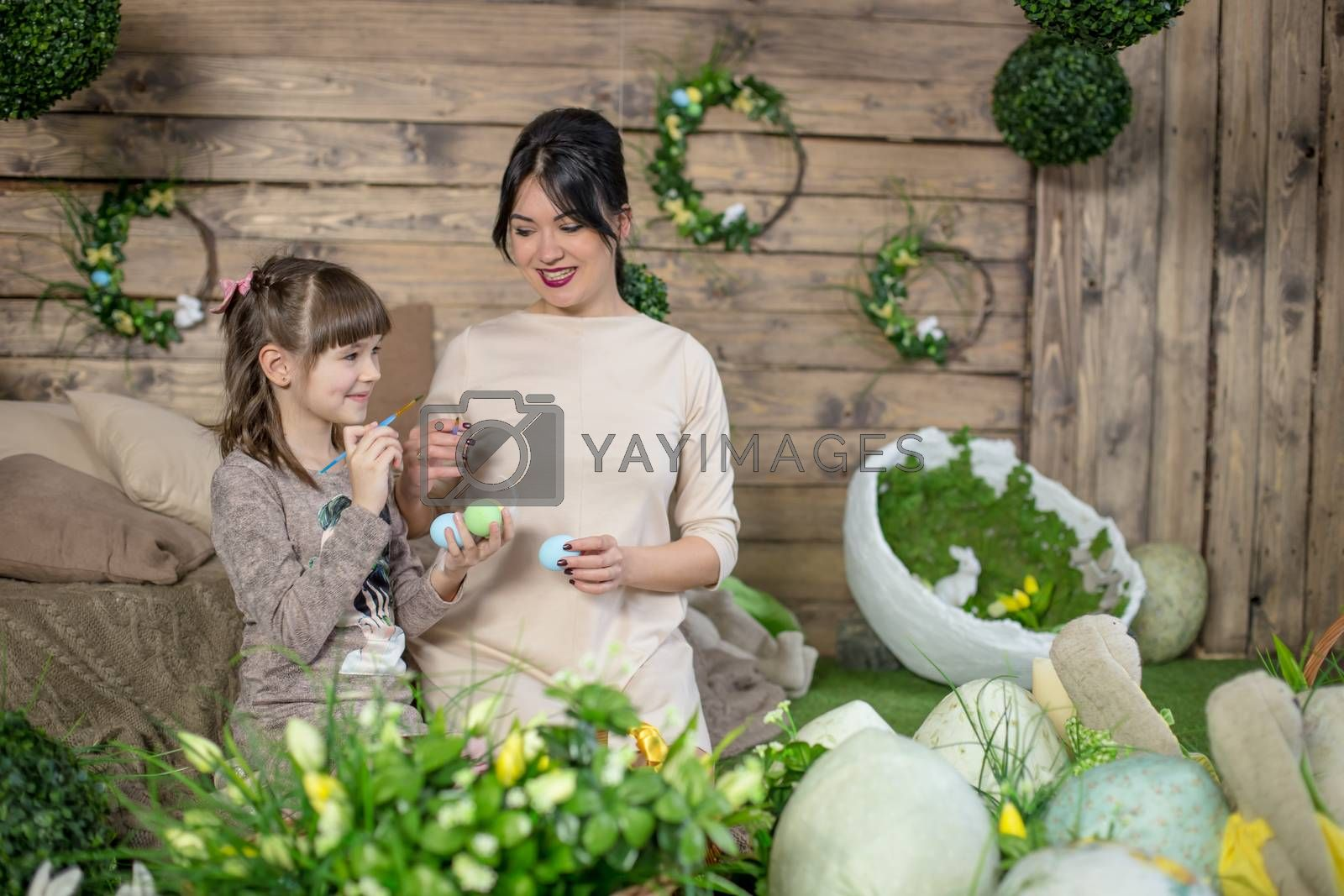 Mother and daughter with Easter eggs in decorated studio