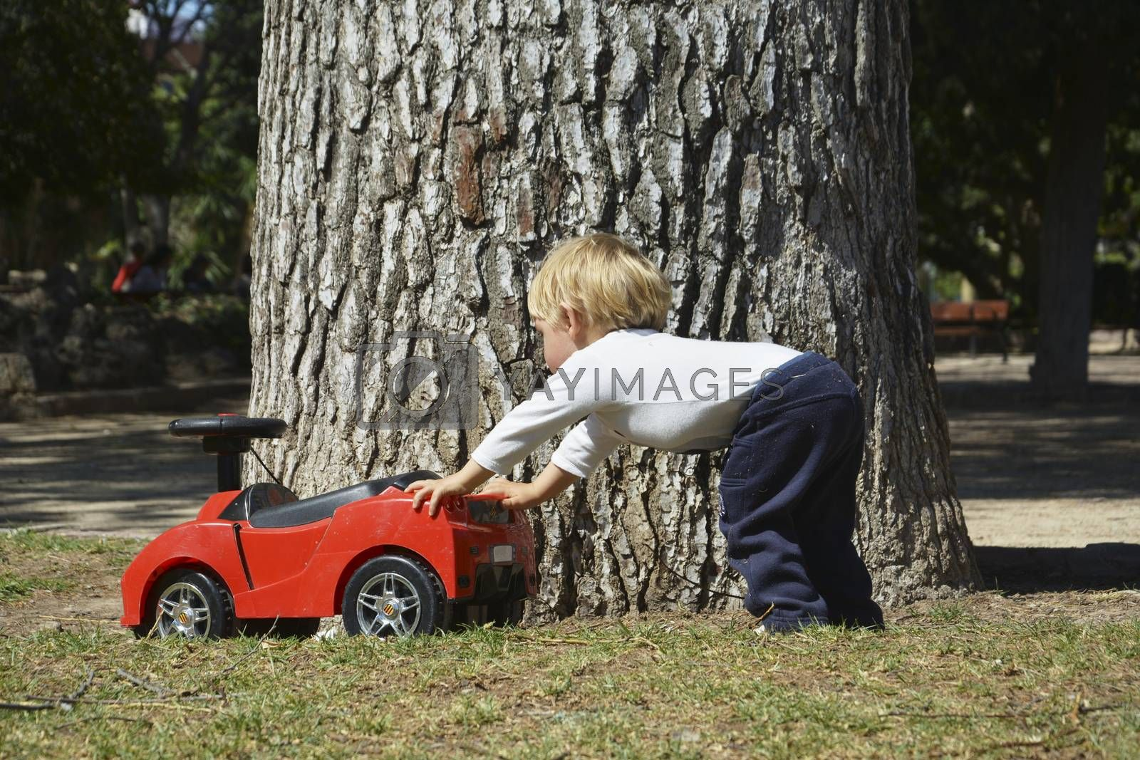 Blond boy playing with his red toy car, Lifestyle