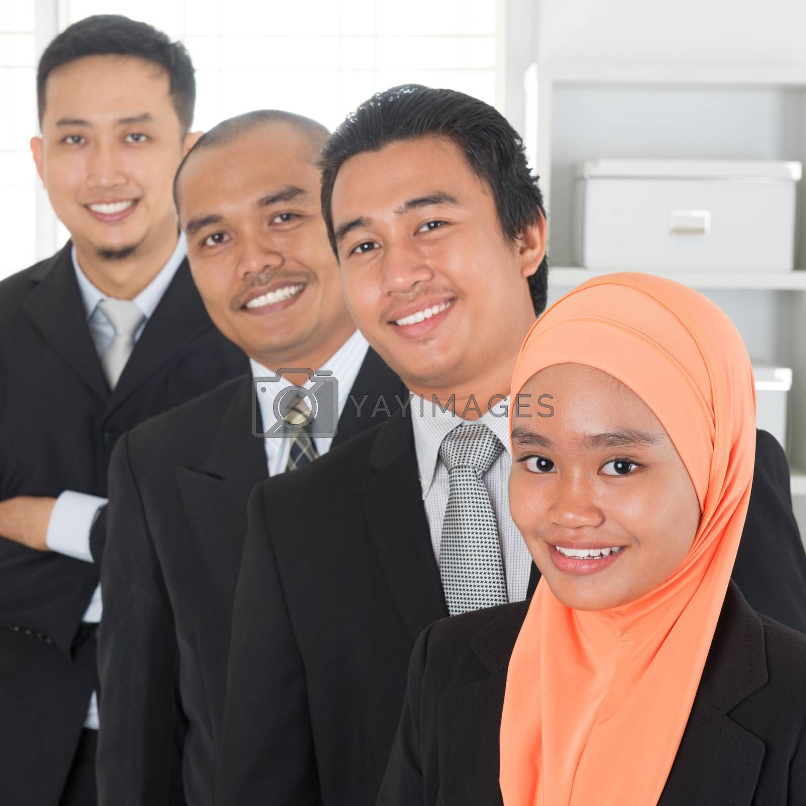 Group of Malaysian businesspeople standing in line inside office room.
