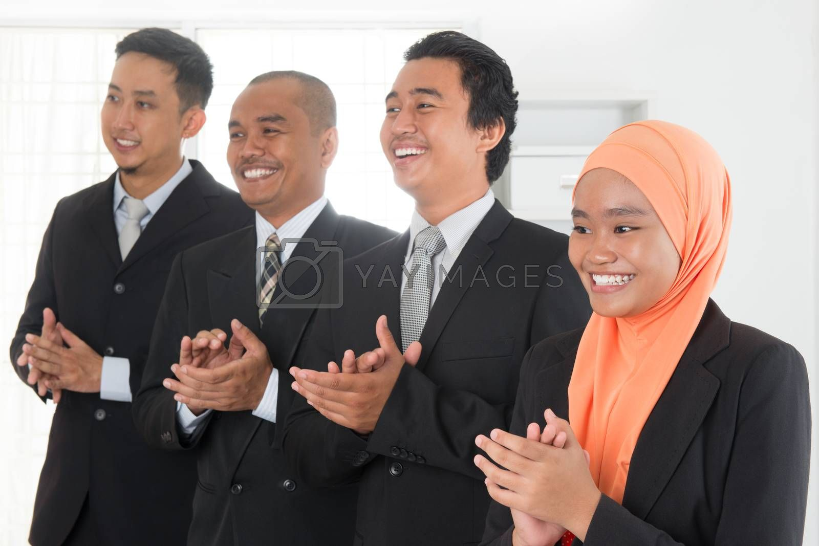 Group of business people standing in line clapping hands inside office room.