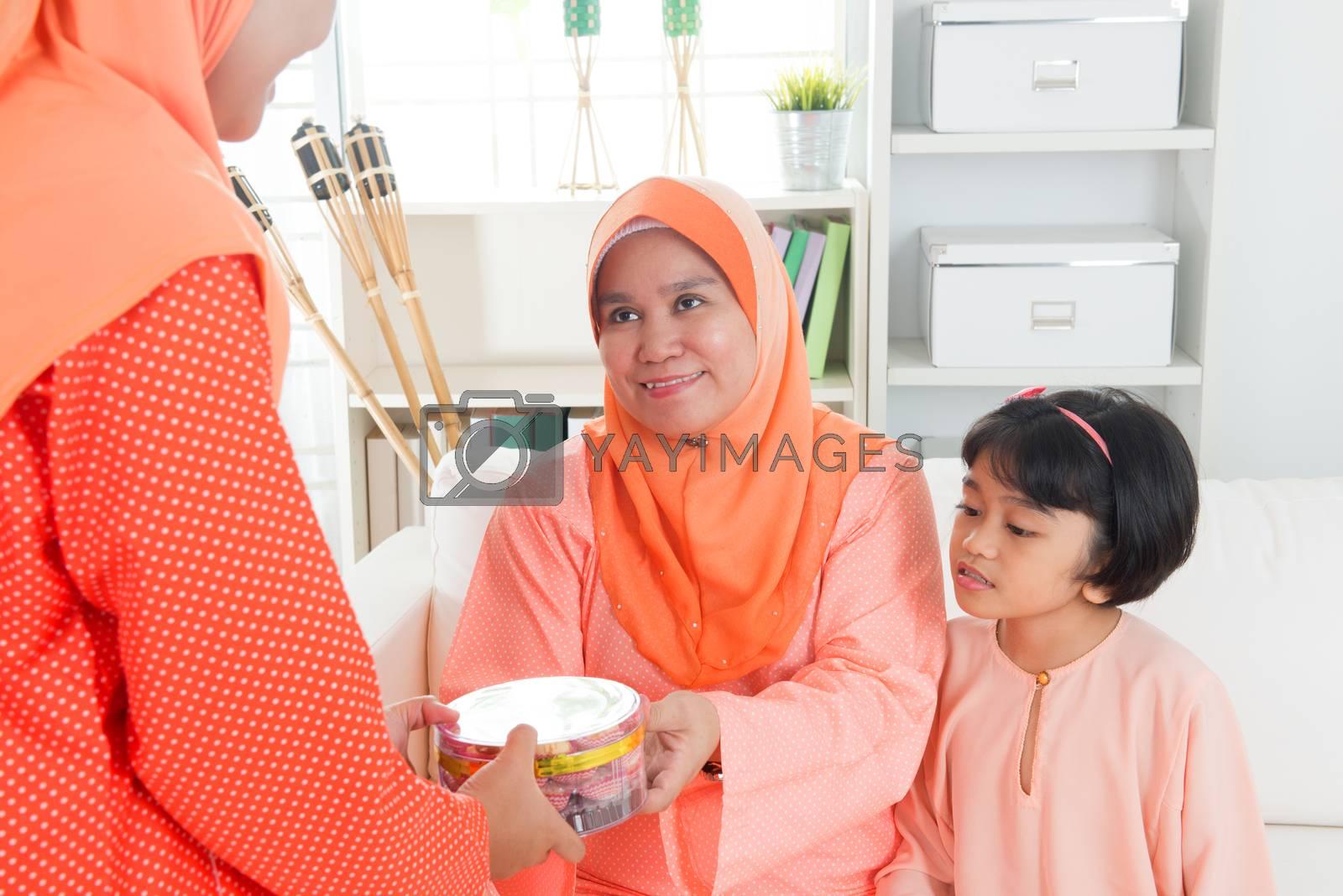 Woman giving elder cookies during Hari Raya. Malay or Malaysian family lifestyle at home.
