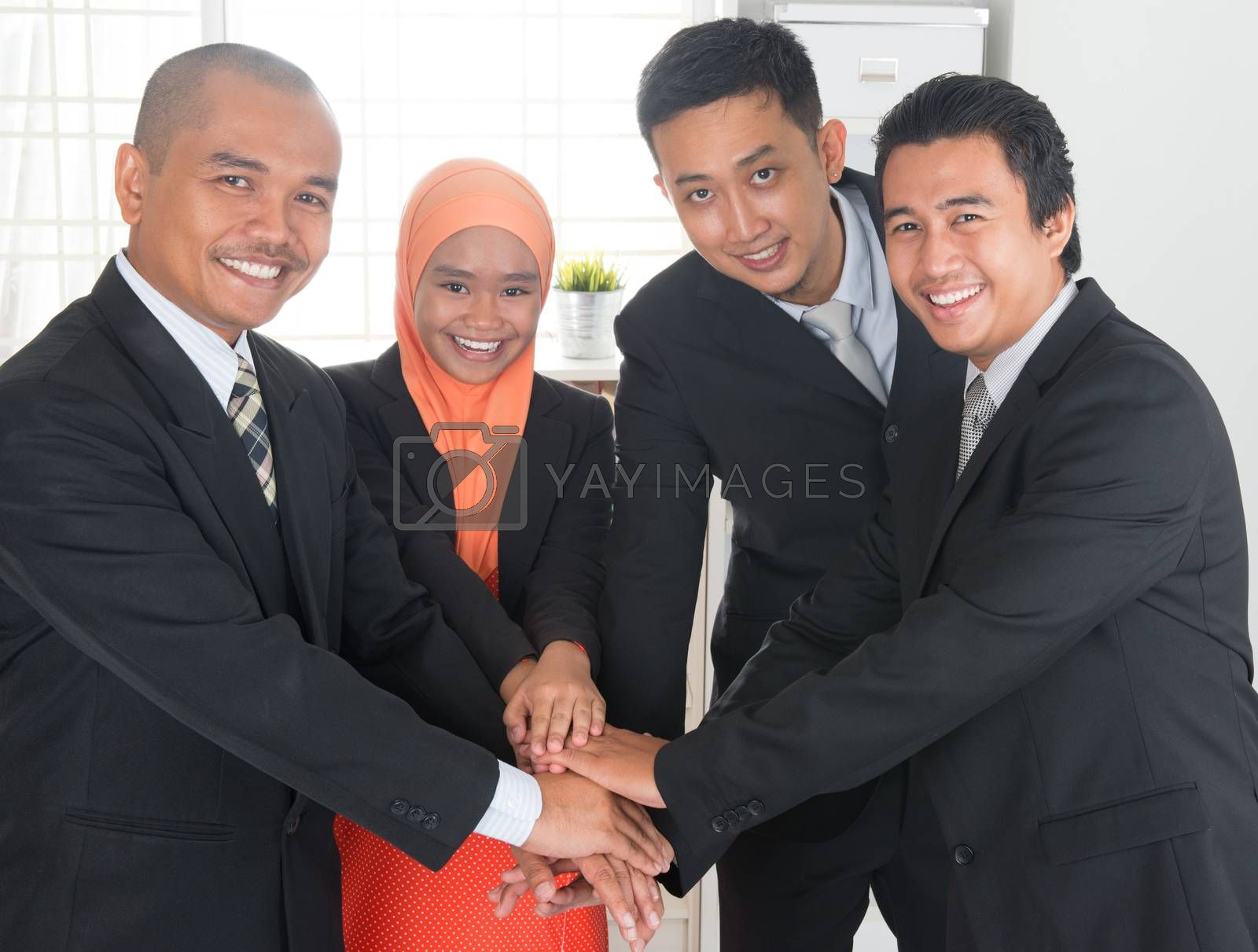 Group of business people having deals and stacking hands inside office room.