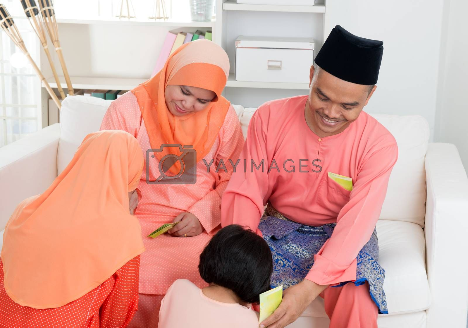 Asian Muslim Malay girl greeting to parents at home during hari raya. Malaysian people living lifestyle.