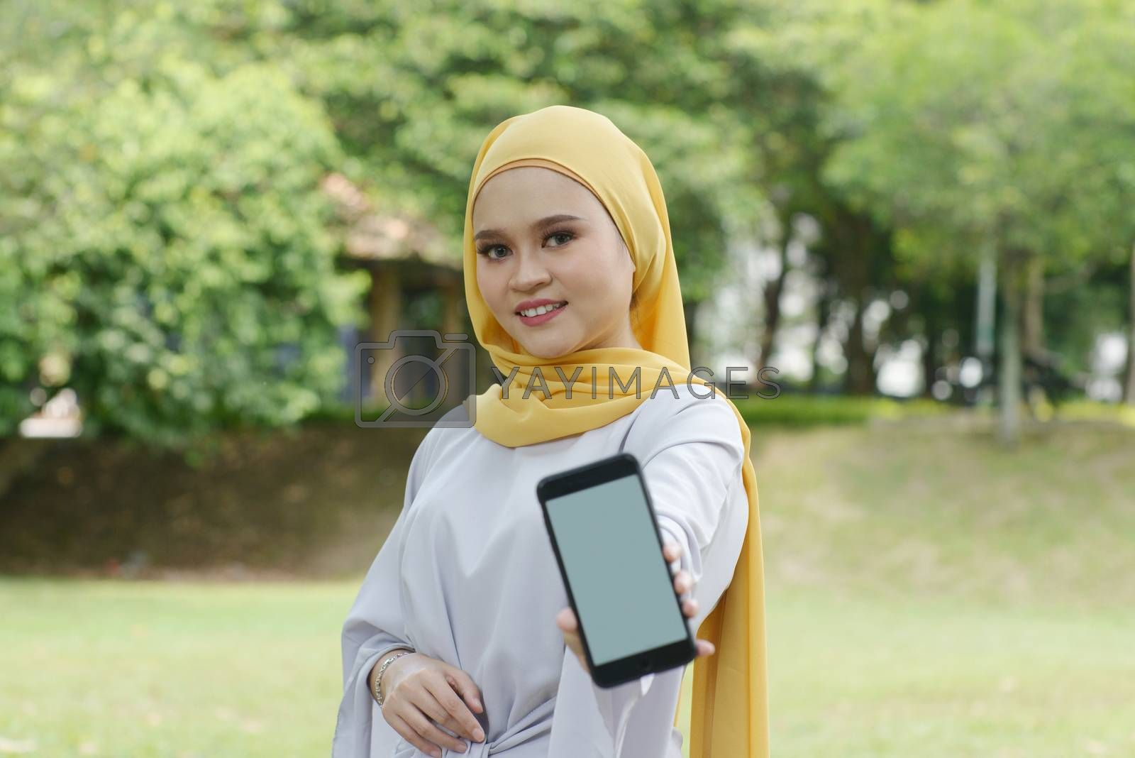 Portrait of cheerful Muslim girl using smartphone, smiling at outdoor.