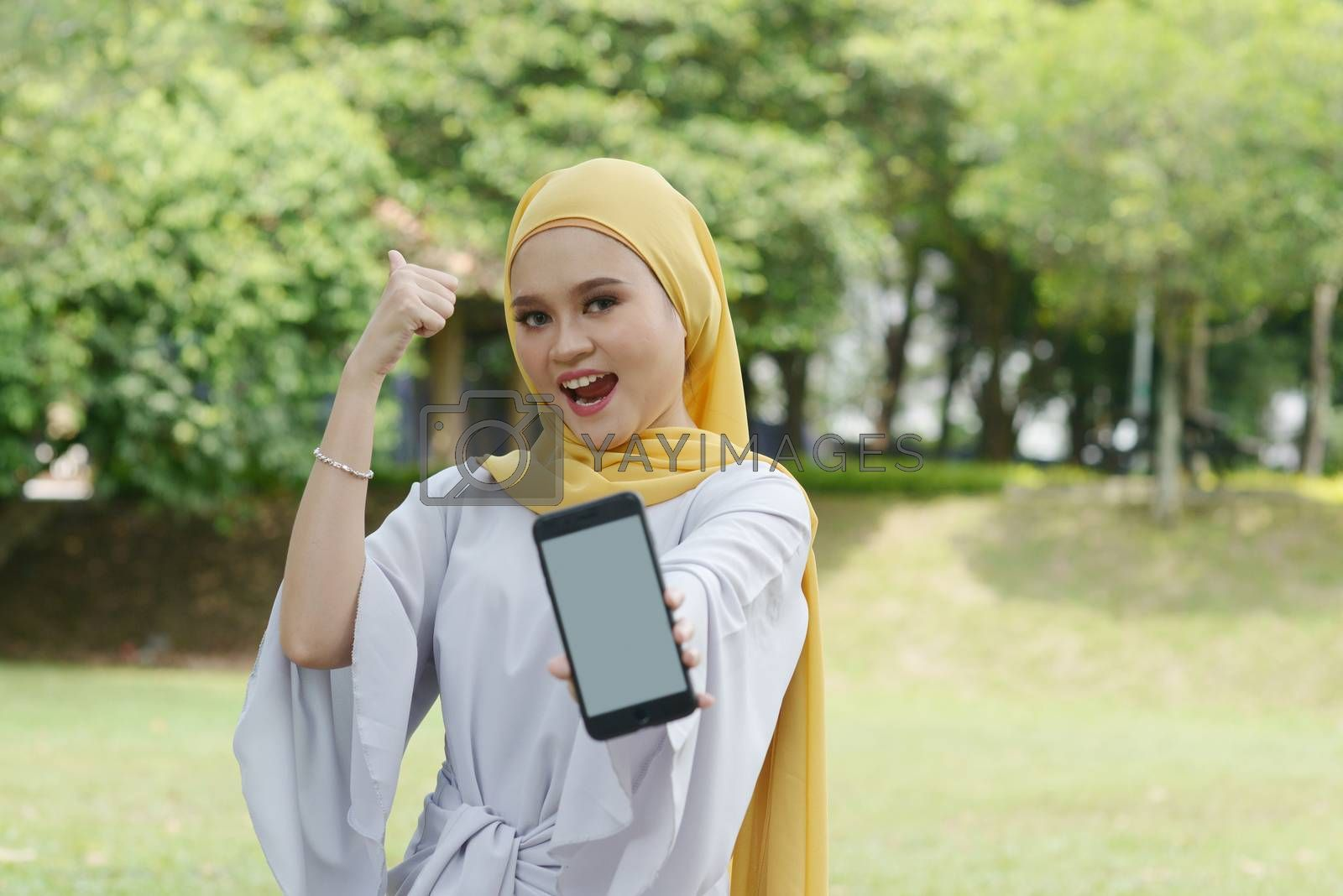 Portrait of cheerful Muslim girl using smartphone and thumb up, smiling at outdoor.
