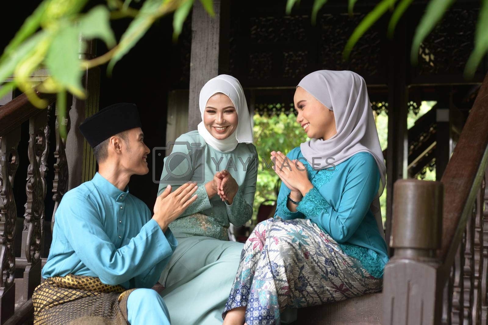 Asian Malay Muslim greetings during Hari Raya Aidilfitri. Malaysian people living lifestyle.