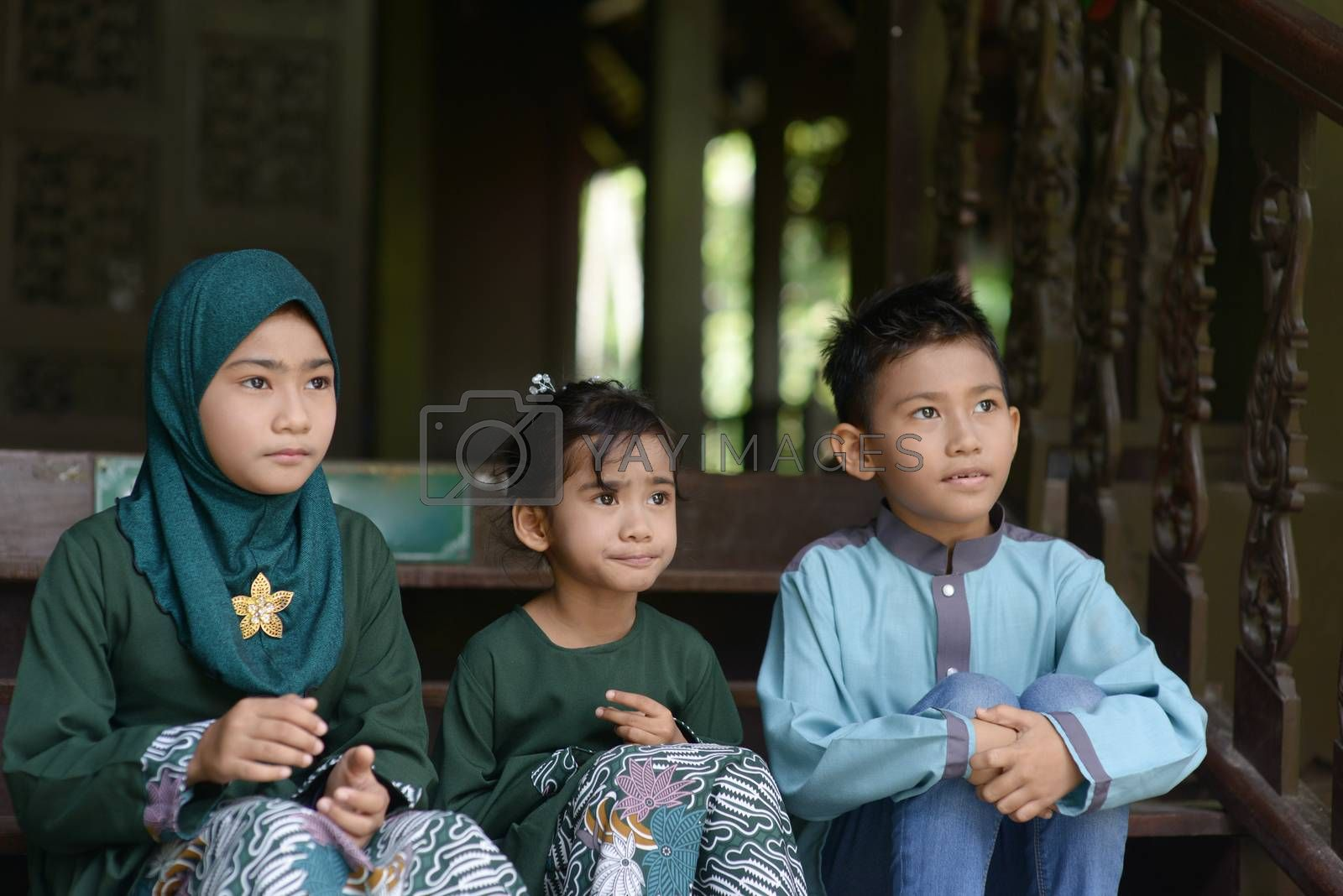 Muslim children sitting and looking away, Hari raya eid al-fitr concept.