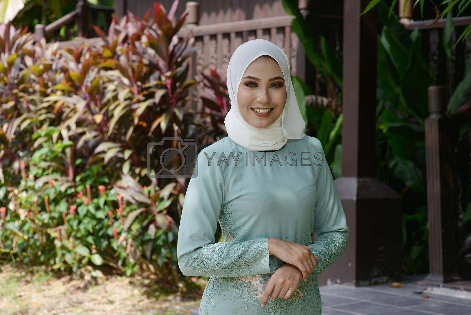 Portrait of Muslim girl in hijab, smiling at outdoor, traditional wooden house background.