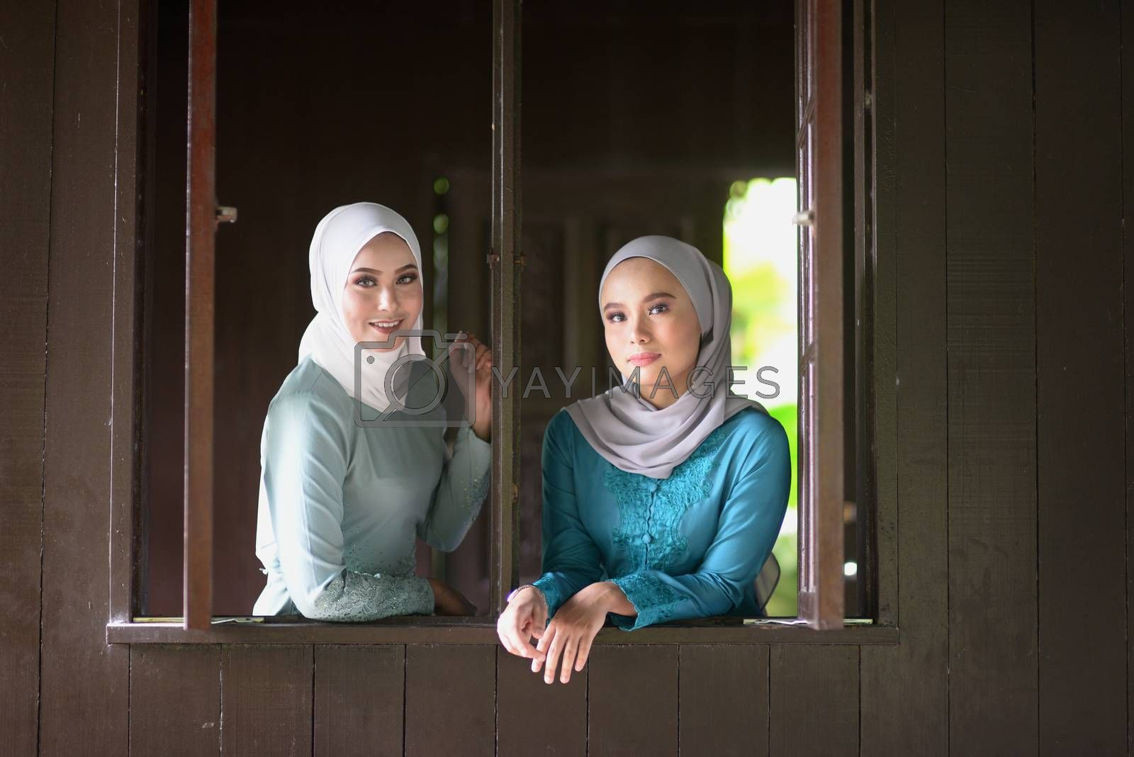 Portrait of Muslim girls in hijab smiling at traditional wooden house.