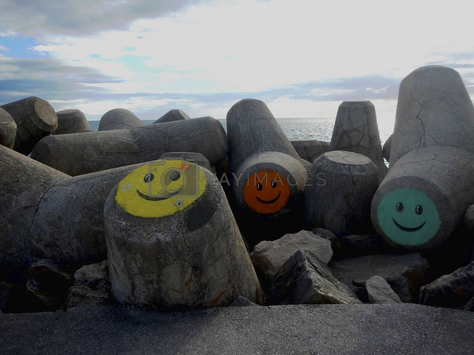 Concrete stones on the beach decorated with colorful faces.
