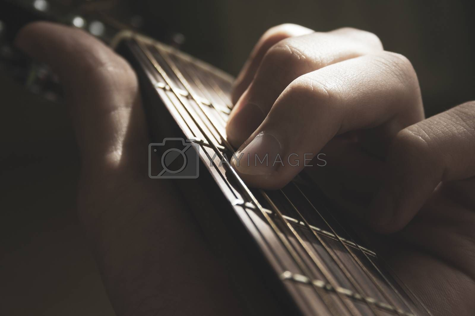 Man's hands fingers on the acoustic guitar strings close up macro shot on sun shine. Music, hobby and leisure, matte toned