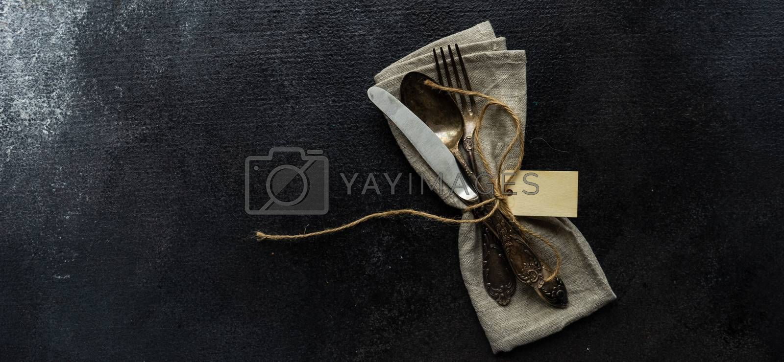 Table setting with cutlery and napkin on concrete background with copy space