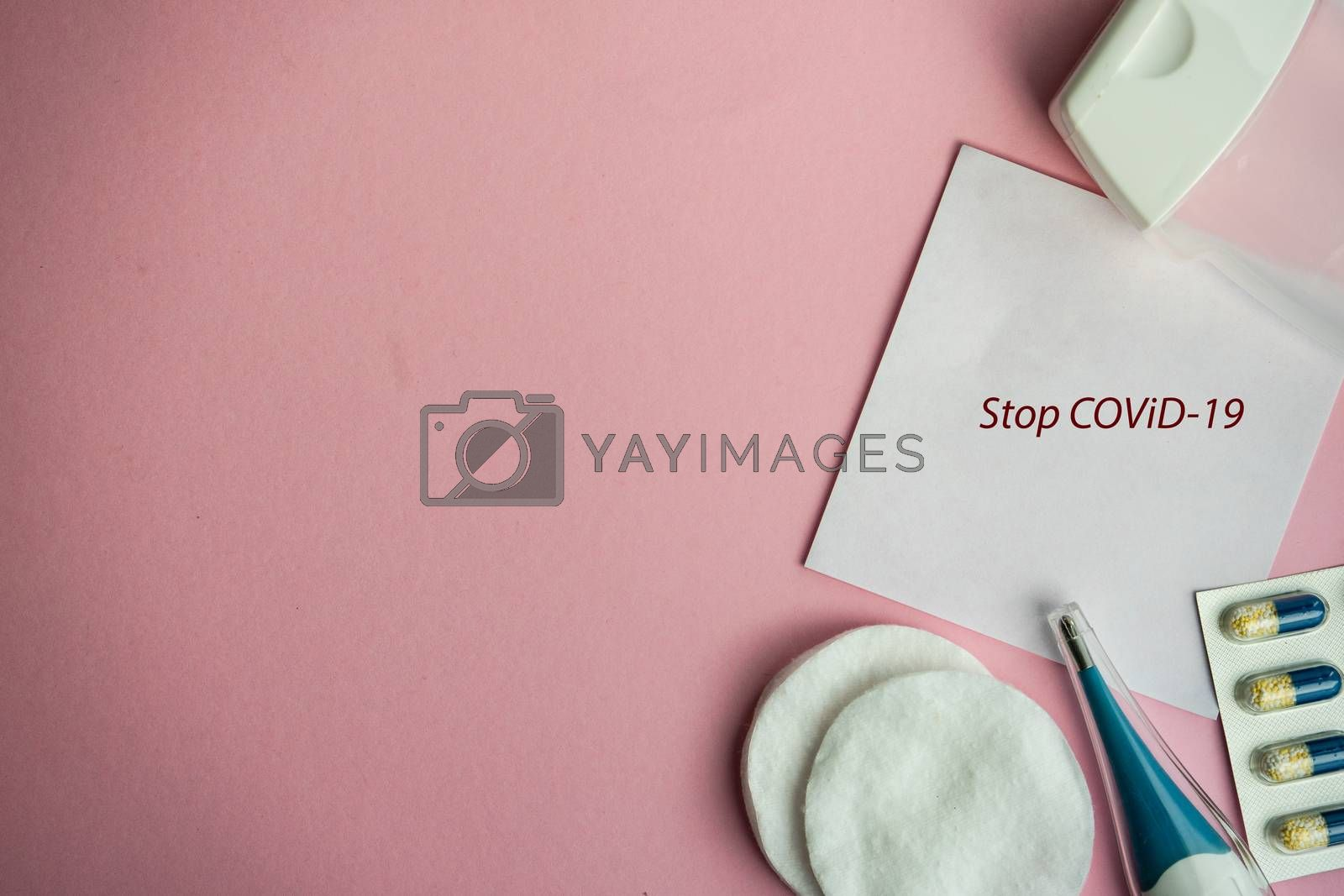 COVID-19 virus concept with pills and other safe staff  on pastel pink background with copy space