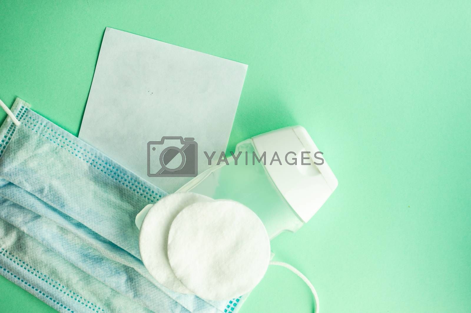 COVID-19 virus concept with face mask and note  on green pastel background with copy space