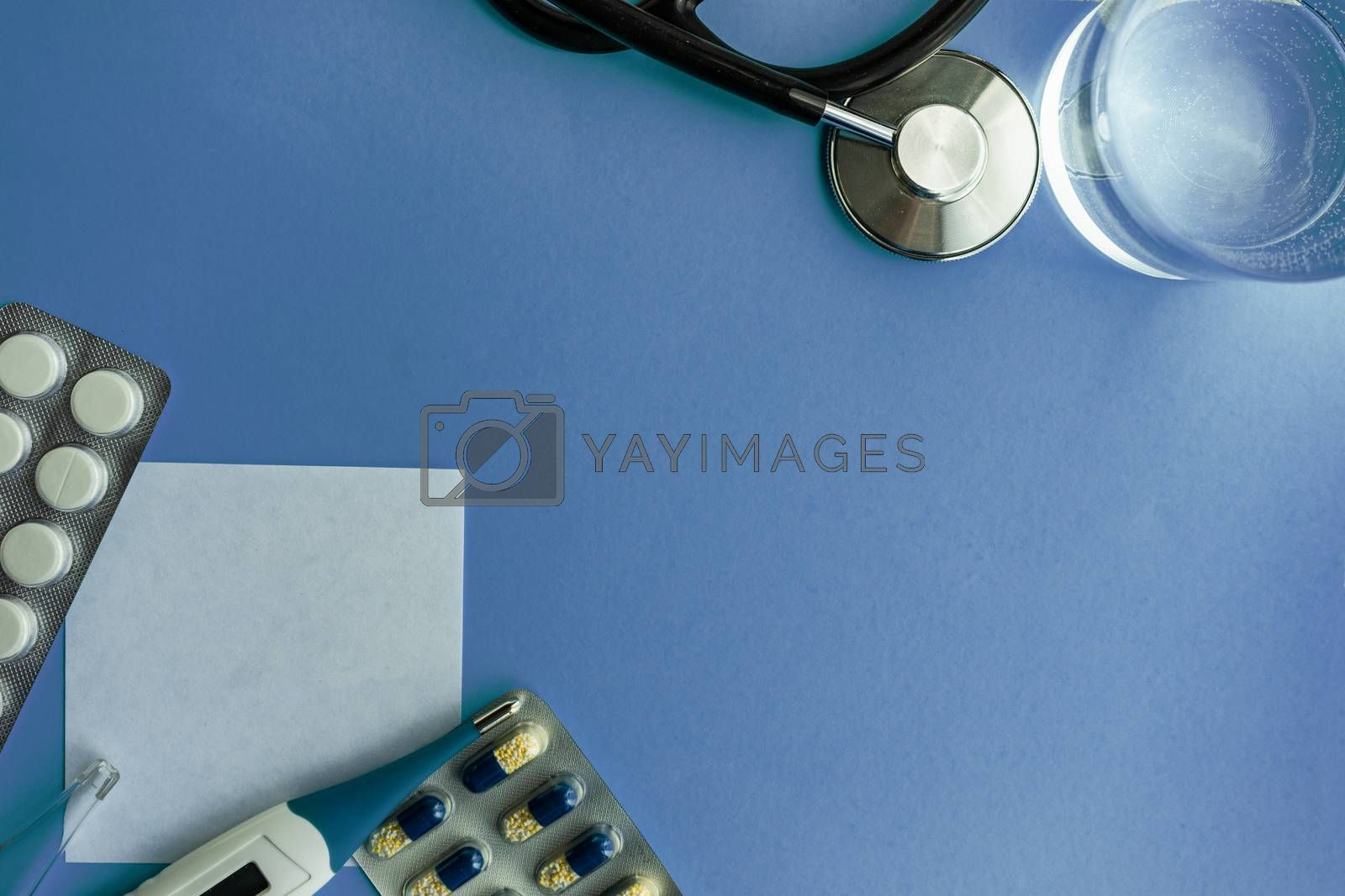 COVID-19 virus concept with glass of water and medicines on pastel background with copy space