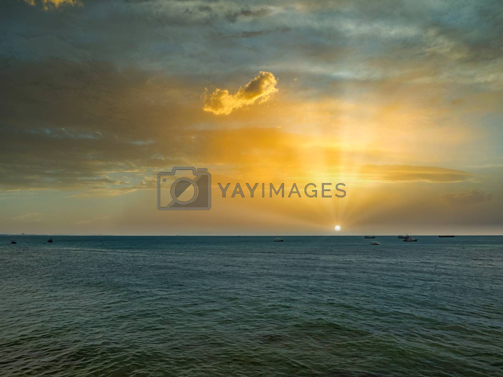 The sun rises above the sea on a bright morning, with fishing boats anchored after returning from fishing.