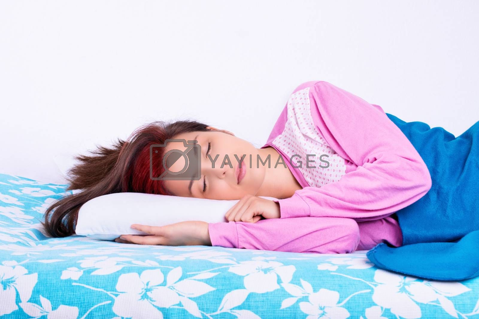 Beautiful young girl in pajamas calmly sleeping in her bed. Beauty sleep concept.