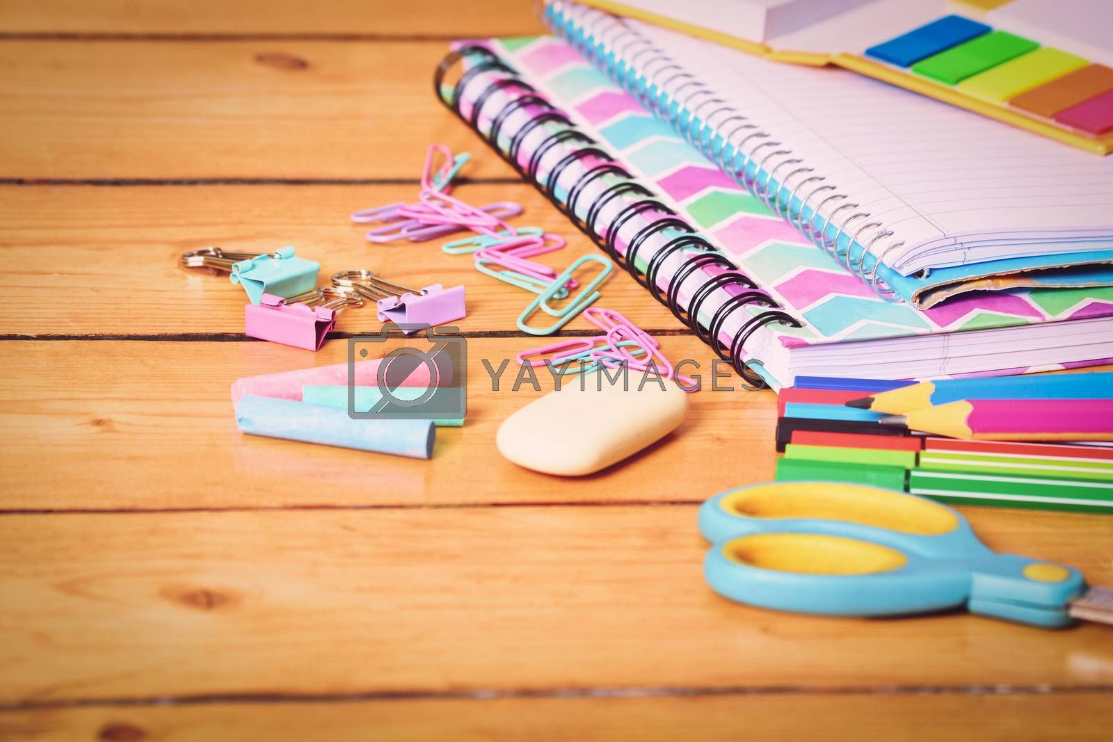 Close up shot of pastel colored girl school stationary on wooden background. Back to school concept.