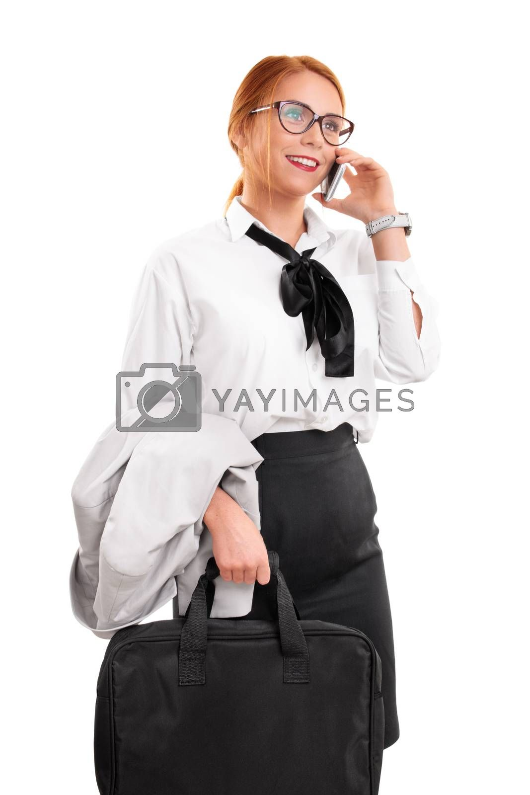 Smiling beautiful young businesswoman with glasses in a suit talking on the phone, holding a laptop bag, isolated on a white background. Business communication concept.